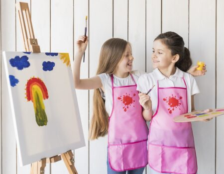portrait-smiling-two-girls-pink-apron-making-fun-while-painting-canvas (1)