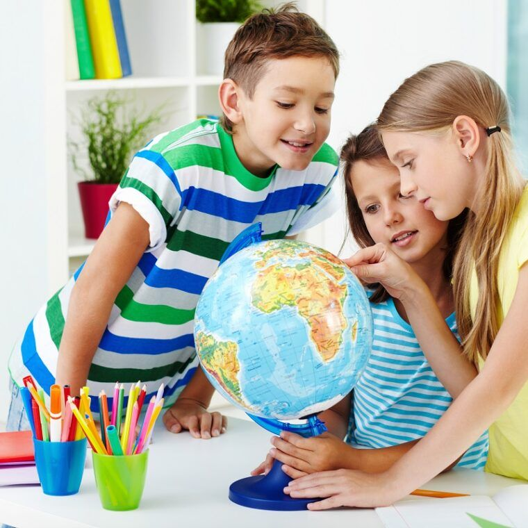 Portrait of happy classmates at workplace studying globe in classroom