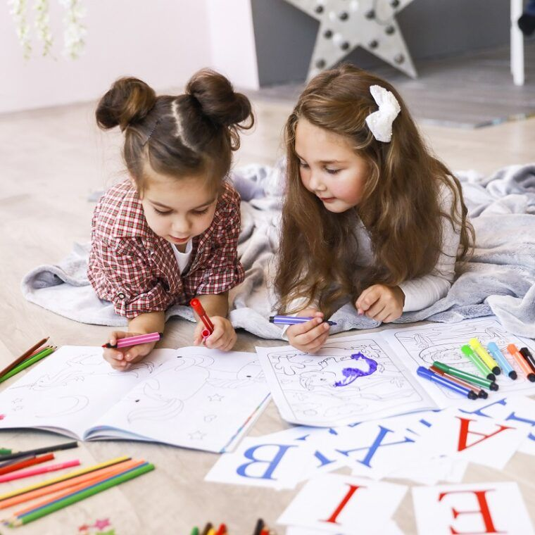 Two tiny cute girls which are drawing in the coloring book laying on the floor on the blanket and learning letters